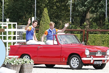 Team Valkenswaard United riders Alberto Zorzi and Marcus Ehning parade the arena aboard a Triumph Classic car